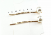 a set of clips with white pearls